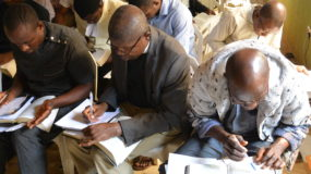 Photo of pastors completing assignments at APT workshop.
