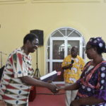 Woman receives graduation certificate and bible